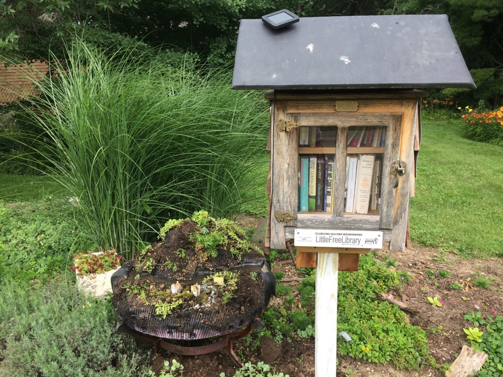 The mini garden sits next to the little library.